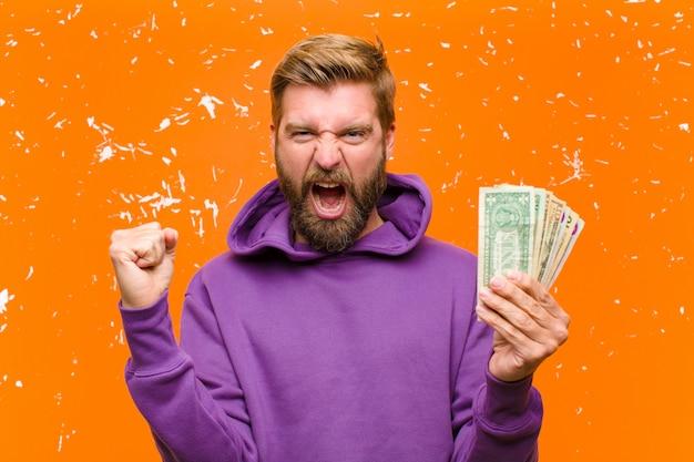 Młody blondynka mężczyzna z banknotów dolarowych lub banknotów na sobie fioletową bluzę z kapturem przed uszkodzoną ścianę pomarańczowy Premium Zdjęcia