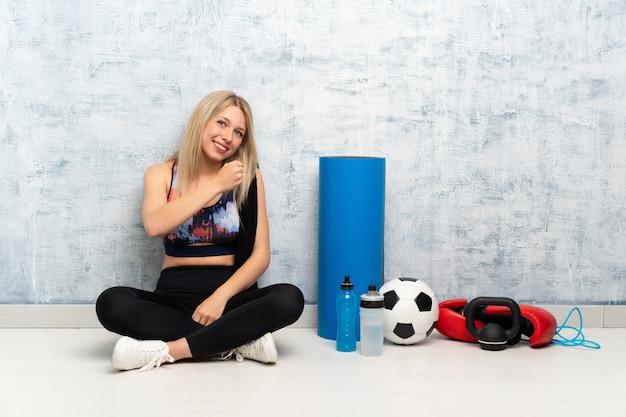 Młody blondynka sporta kobiety obsiadanie na podłoga świętuje zwycięstwo Premium Zdjęcia