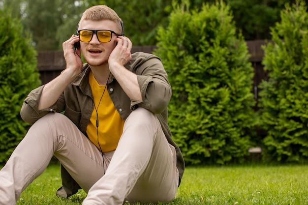 Młody Brodaty Facet W żółtych Okularach Niedbale Ubrany Siedzi Na Trawie, Słuchając Muzyki W Słuchawkach I Radośnie śpiewa Z Zamkniętymi Oczami Na Zielonym Tle. Skopiuj Miejsce Premium Zdjęcia