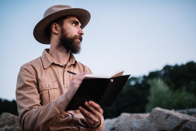 Młody Brodaty Mężczyzna Jest Ubranym Modnisia Writing Kapeluszowe Notatki W Notepad, Planuje Podróż Premium Zdjęcia