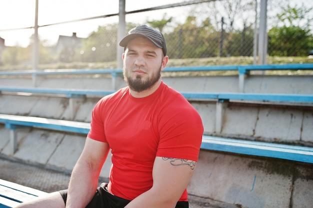 Młody Brodaty Muskularny Mężczyzna Nosić Czerwoną Koszulę, Szorty I Czapkę Na Stadionie Premium Zdjęcia