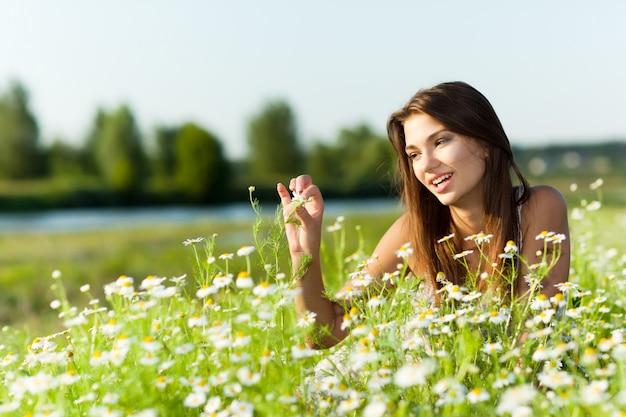 Młody Brunetki Kobiety Lying On The Beach Na Trawie I Ono Uśmiecha Się Na Letnim Dniu Z Zieloną Naturą I Rzeką Przy Tłem Premium Zdjęcia