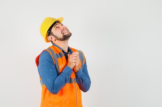 Młody Budowniczy, ściskając Ręce W Geście Modlitwy W Koszuli Darmowe Zdjęcia