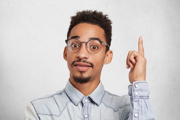 Młody, Bystry Student Nosi Okulary I Dżinsową Koszulę, Podnosi Palec Wskazujący, Gdy Wpada Na Pomysł Darmowe Zdjęcia