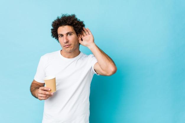 Młody Caucasian Kędzierzawy Mężczyzna Trzyma Na Wynos Kawę Próbuje Słuchać Plotki. Premium Zdjęcia