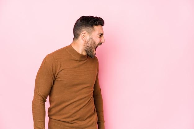 Młody Caucasian Mężczyzna Przeciw Różowemu Tłu Odizolowywał Krzyczeć W Kierunku Odbitkowej Przestrzeni Premium Zdjęcia