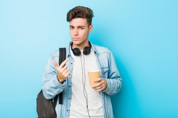 Młody Caucasian Studencki Mężczyzna Trzyma Na Wynos Kawę Wskazuje Z Palcem Na Ciebie, Jakby Zapraszający Zbliżał Się. Premium Zdjęcia