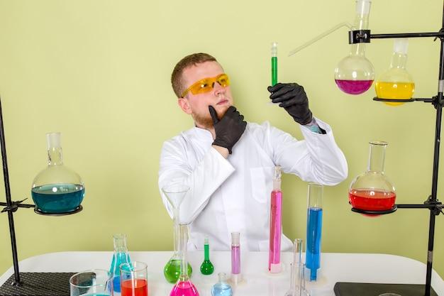 Młody Chemik Z Przodu Patrząc Na Zielony środek Chemiczny W Pomarańczowych Okularach Ochronnych Darmowe Zdjęcia