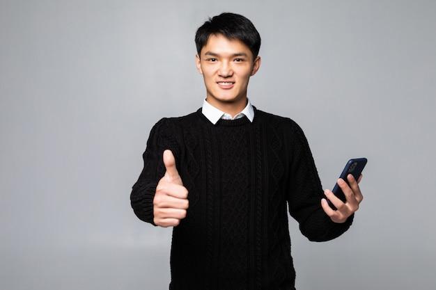 Młody Chiński Mężczyzna Opowiada Na Smartphone Stać Szczęśliwy Z Dużym Uśmiechem Robi Ok Znakowi, Kciuk Up Z Palcami, Znakomity Podpisuje Odosobnioną Biel ścianę Darmowe Zdjęcia