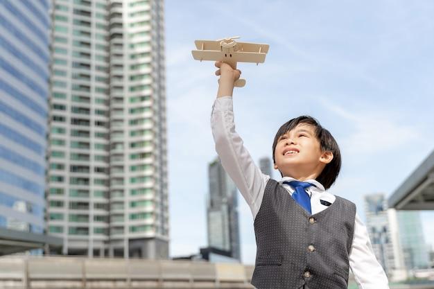 Młody Chłopak Gra Wyobraźnia Lotnika Zabawka Samolot Marzy O Byciu Pilotem Przyszłości W Biznesowej Dzielnicy Miasta Darmowe Zdjęcia