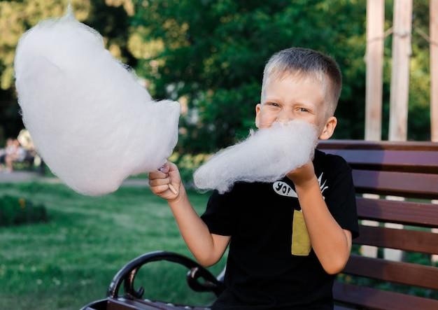 Młody Chłopak Je Wata Cukrowa Z Lepkiego Cukru Wirowanego Siedzącego Na ławce W Parku Premium Zdjęcia