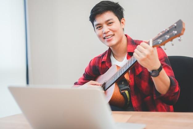 Młody Chłopak Nastolatek Azjatyckich Otworzyć Laptopa Do Wyszukiwania Piosenki I Gry Na Gitarze Klasycznej Premium Zdjęcia