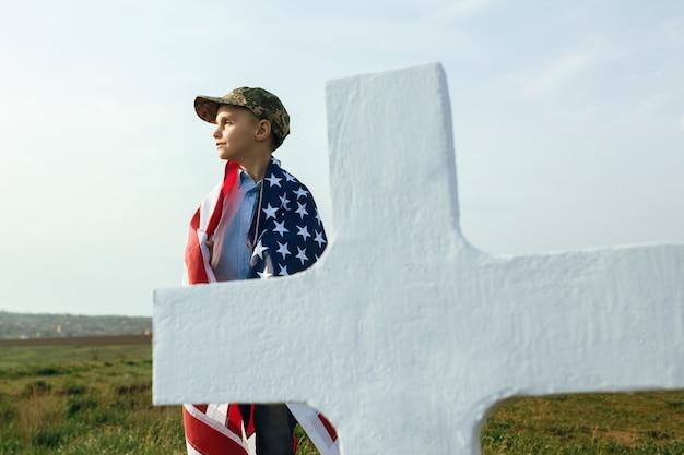 Młody Chłopak W Czapce Wojskowej Przy Grobie Ojca W Dniu Pamięci Premium Zdjęcia