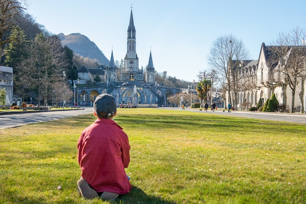 Młody Chłopak Z Katedrą-sanktuarium W Lourdes (francja) Premium Zdjęcia