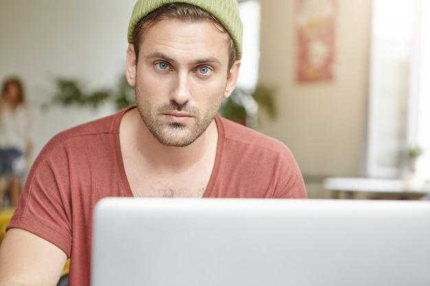 Młody Chłopak Z Niebieskimi Oczami I Brodą Wygląda Pewnie, Gdy Siedzi Przed Otwartym Laptopem, Sprawdza Pocztę E-mail Lub Surfuje Po Sieciach Społecznościowych Online Darmowe Zdjęcia