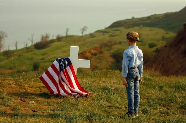 Młody Chłopiec W Czapce Wojskowej Pozdrawia Grób Ojca W Dzień Pamięci Premium Zdjęcia