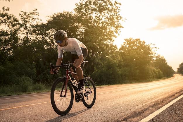 Młody Cyklista Jedzie Rower Na Otwartej Drodze Przy Zmierzchem Premium Zdjęcia