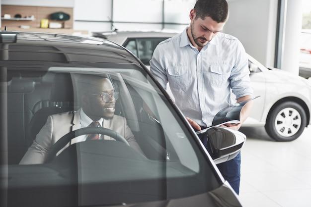 Młody Czarny Biznesmena Testa Przejażdżki Nowy Samochód. Bogaty Afroamerykanin Premium Zdjęcia
