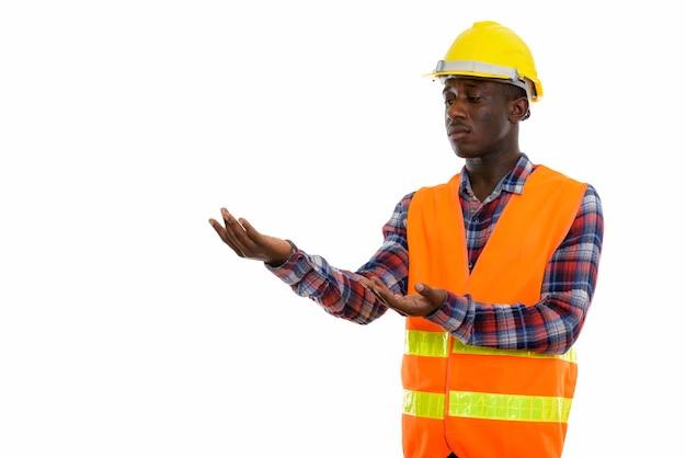 Młody Czarny Człowiek Afrykański Pracownik Budowlany Pokazując Coś Premium Zdjęcia