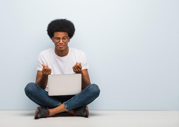 Młody czarny człowiek siedzi na podłodze z laptopem robi gest potrzeby Premium Zdjęcia