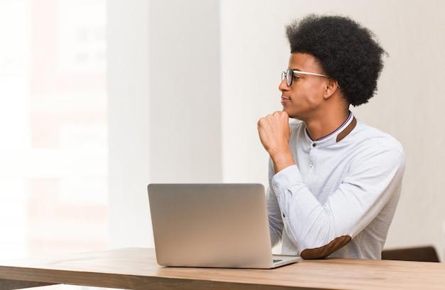 Młody czarny człowiek za pomocą swojego laptopa na stronie patrząc z przodu Premium Zdjęcia