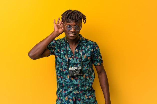 Młody Czarny Rasta Mężczyzna W Wakacyjnym Spojrzeniu Próbuje Słuchać Plotek. Premium Zdjęcia