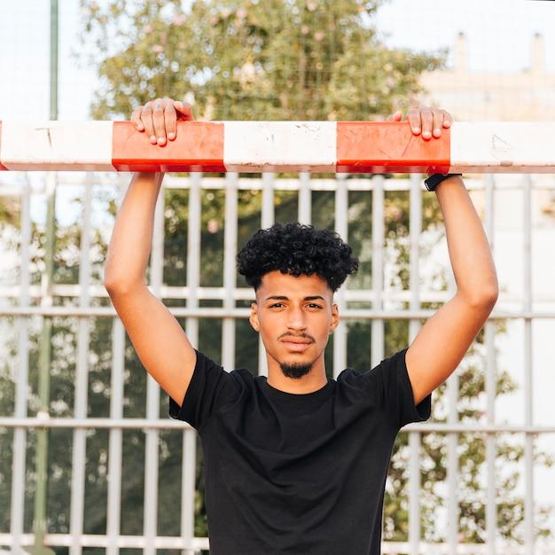Młody czarny sportowiec trzyma na futbolowym celu przy stadium Darmowe Zdjęcia