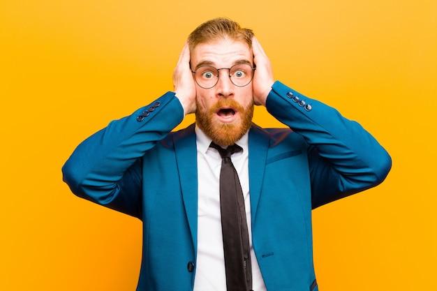 Młody Czerwony Biznesmen Głowy Wyglądający Nieprzyjemnie Zszokowany, Przestraszony Lub Zmartwiony, Z Szeroko Otwartymi Ustami I Zakrywający Oba Uszy Rękami Przed Pomarańczową ścianą Premium Zdjęcia