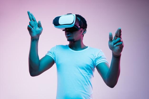 Młody Człowiek Afro-amerykański, Wskazując I Używając Okularów Vr W świetle Neonu Na Gradientowym Tle. Portret Mężczyzny. Pojęcie Ludzkich Emocji, Wyrazu Twarzy, Nowoczesnych Gadżetów I Technologii. Darmowe Zdjęcia
