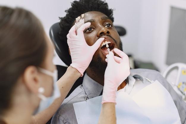Młody Człowiek Afroamerykanin. Facet Odwiedzający Gabinet Dentystyczny W Celu Zapobiegania Jamy Ustnej. Mężczyzna I Znany Lekarz Podczas Kontroli Zębów. Darmowe Zdjęcia