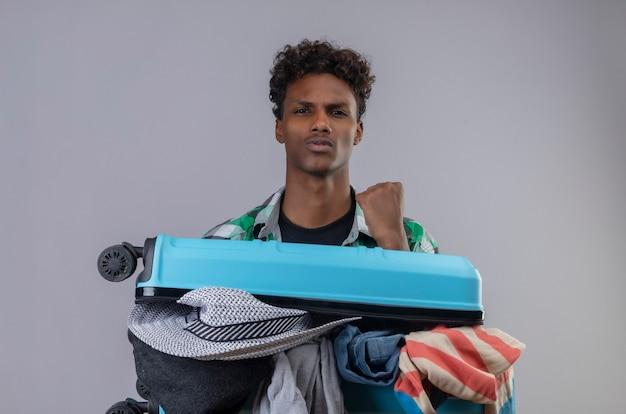 Młody Człowiek Afroamerykanin Podróżnik Z Walizką Pełną Ubrań, Podnosząc Pięść, Patrząc Pewnie, Ciesząc Się Swoim Sukcesem Darmowe Zdjęcia