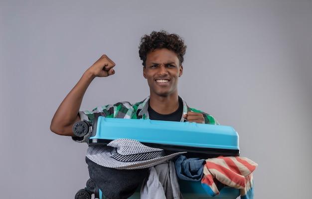 Młody Człowiek Afroamerykański Podróżnik Z Walizką Pełną Ubrań, Podnosząc Pięść Szczęśliwy I Wyszedł, Ciesząc Się Swoim Sukcesem Darmowe Zdjęcia