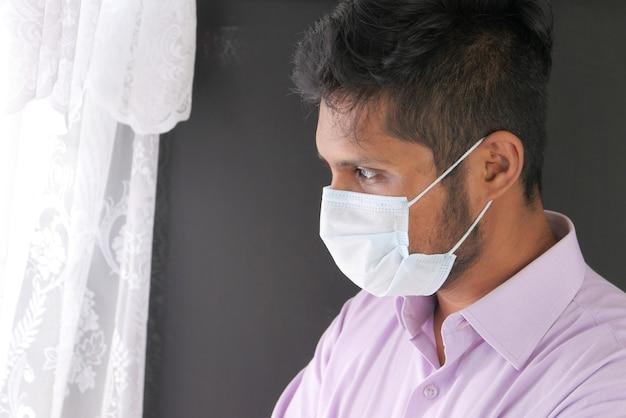 Młody Człowiek Azjatyckich Z Maską Ochronną W Twarz Patrząc Przez Okno Premium Zdjęcia