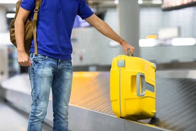 Młody Człowiek Bierze Bagaż Od Paska Przy Lotniskiem Premium Zdjęcia