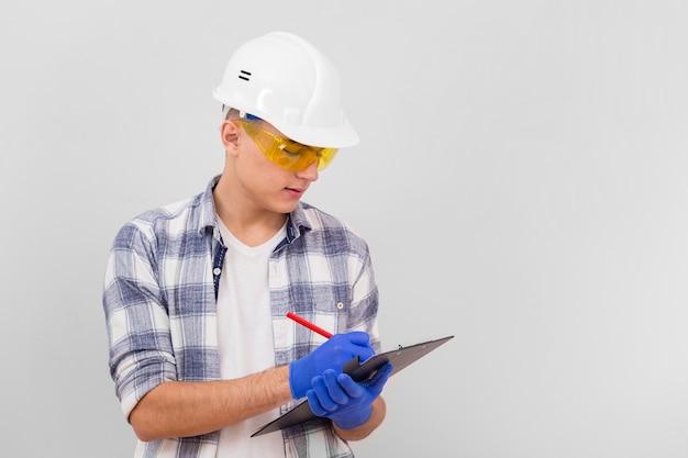 Młody Człowiek Bierze Notatki Na Schowku Z Kopii Przestrzenią Premium Zdjęcia