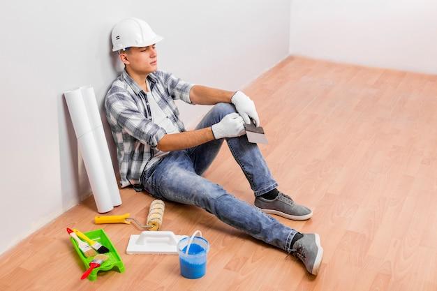 Młody Człowiek Bierze Przerwę Podczas Gdy Siedzący Na Podłoga Darmowe Zdjęcia