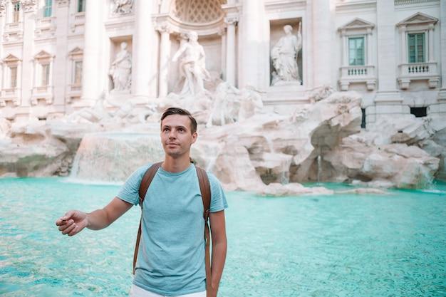 Młody człowiek blisko fontanny fontana di trevi z monetami w rękach Premium Zdjęcia