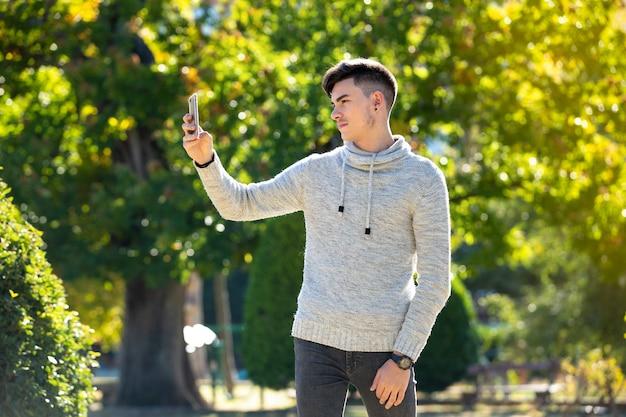Młody Człowiek Co Selfie W Parku W Zimny Słoneczny Dzień Premium Zdjęcia