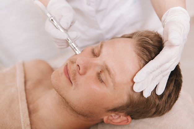 Młody Człowiek Coraz Zabieg Pielęgnacji Skóry Twarzy Przez Kosmetologa Premium Zdjęcia