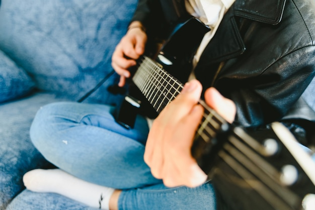 Młody Człowiek ćwiczy Z Jego Gitarą Elektryczną Na Kanapie Jego Domowa Uczenie. Premium Zdjęcia