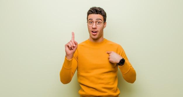 Młody Człowiek Czuje Się Dumny I Zaskoczony, Wskazując Na Siebie Pewnie, Czując Się Jak Odnoszący Sukcesy Numer Jeden Na ścianie Premium Zdjęcia