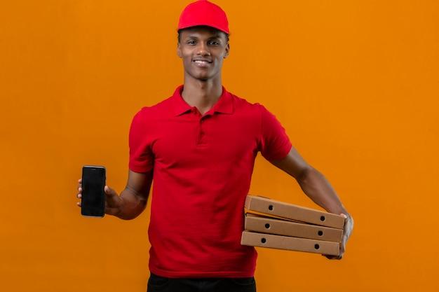 Młody Człowiek Dostawy Afroamerykanów Na Sobie Czerwoną Koszulkę Polo I Czapkę Gospodarstwa Stos Pudełek Po Pizzy I Pokazując Smartfon W Ręku Do Kamery Z Uśmiechem Na Twarzy Na Białym Tle Pomarańczowy Darmowe Zdjęcia