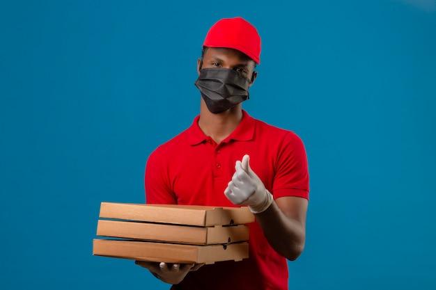 Młody Człowiek Dostawy Afroamerykanów Na Sobie Czerwoną Koszulkę Polo I Czapkę W Maskę Ochronną I Rękawiczki, Stojąc Z Stos Pudełek Po Pizzy Robi Gest Pieniędzy Na Białym Darmowe Zdjęcia