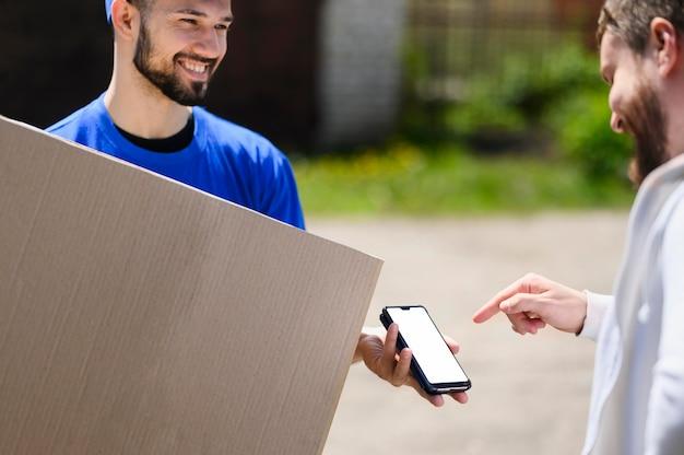 Młody Człowiek Dostawy Czeka Na Klienta, Aby Potwierdzić Wysyłkę Darmowe Zdjęcia