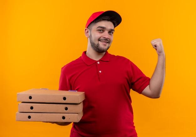 Młody Człowiek Dostawy W Czerwonym Mundurze I Czapce, Trzymając Stos Pudełek Po Pizzy, Patrząc Pewnie I Uśmiechając Się, Wskazując Do Tyłu Darmowe Zdjęcia