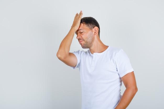 Młody Człowiek Dotyka Czoła Dłonią W Białej Koszulce I Szuka Zapominalski Widok Z Przodu. Darmowe Zdjęcia