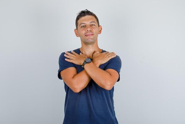 Młody Człowiek Dotyka Ramion Skrzyżowanymi Rękami W Widoku Z Przodu Granatowej Koszulki. Darmowe Zdjęcia