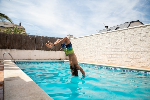 Młody człowiek fitness, skoki do wody w basenie jednego dnia wakacji Premium Zdjęcia