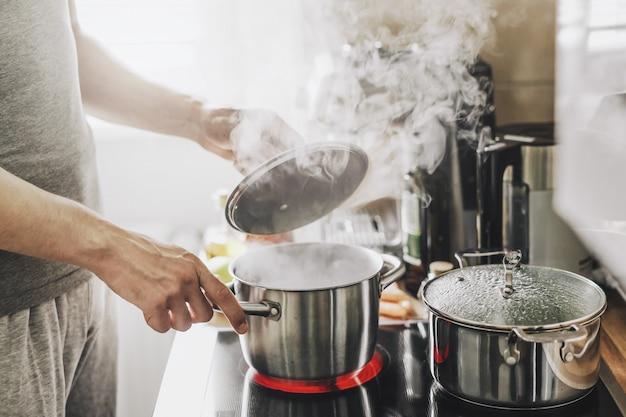 Młody Człowiek Gotowanie świeżej żywności W Domu I Otwieranie Pokrywy Garnka Na Parze. Darmowe Zdjęcia