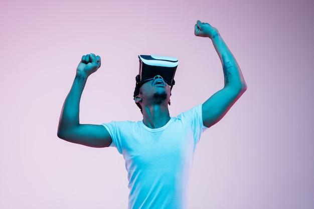Młody Człowiek Gra I Używa Okularów Vr W świetle Neonowym Na Gradiencie Darmowe Zdjęcia